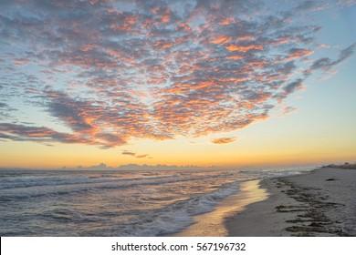 Bright dawn over Mediterranean Sea with long sand beach. Nei Pori village, Pieria, Greece.