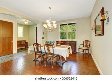 Bright dining area in old house. View of old dining table set and cabinet