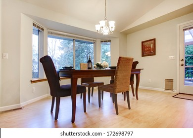Bright dining room with a wooden table set and wicker chairs