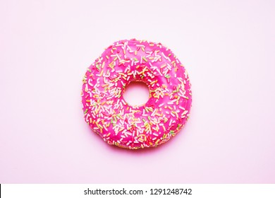 Bright donut in a pink glaze with a multi-colored rainbow sprinkle on a pink background. Sweets and desserts. Minimalistic background with clean place for the inscription. Copy space. Soft focus.