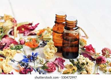 Bright dried medicinal herbs and flowers for cosmetic and healthcare use. Apothecary aroma dropper bottles. Natural herbal body balm