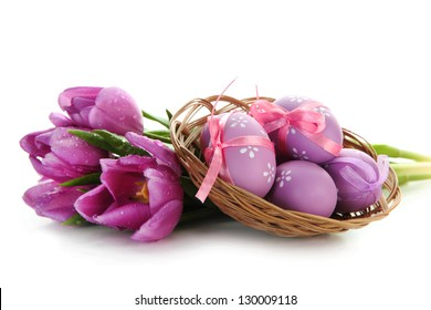 Bright easter eggs in basket and tulips, isolated on white