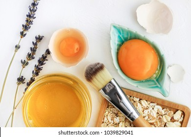 Bright egg yolks, oatflakes, honey, lavender with cosmetic brush closeup, natural holistic ingredients for homemade beauty care. Fresh products for glowing skin. White background viewed above.