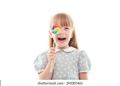 Bright emotions. Nice fair-haired little girl holding colorful candy in front of her face and closing the eye while laughing.