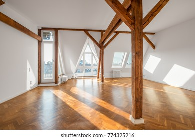 bright, empty penthouse loft room with parquet floor and wooden framework -