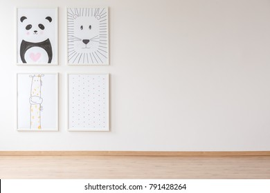 Bright empty room interior for newborn baby with four posters with animals and dots hanging on the wall with copy space