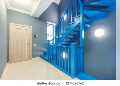 Bright entryway with laminate flooring, high ceiling, front door and staircase with wood railings. Deep blue wooden staircase