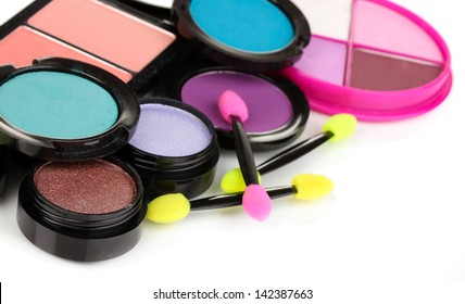 Bright eye shadows and sponge brushes for foundation isolated on white