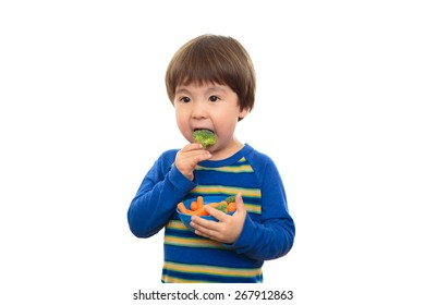 Bright eyed three year old boy eating broccoli and carrots on, isolated on a white background. Little child eating healthy food and vegetables, holding a blue bowl of snacks. Happy and healthy living.