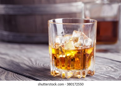 Bright faceted glass of whiskey on background  barrel and decanter