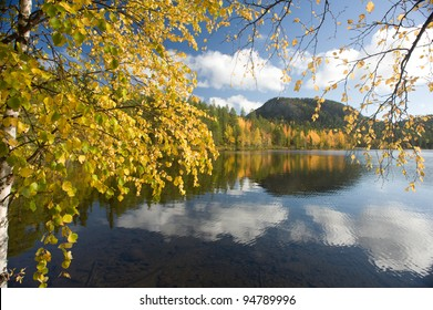 Bright fall colors, crystal clear lake and rocky hill in the background.