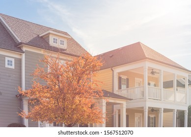 Bright fall foliage near typical two story country-style residential house in suburbs Dallas. White painted porch patio with banister, dormer roof and outdoor ceiling fan on second floor