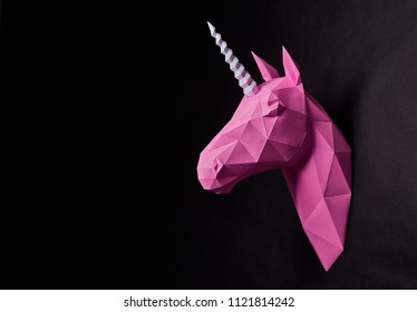 Bright fancy pink origami unicorn's head. Hanging on saturated black wall. Dull colored. Dark background. Innovative interior design details. Straight lines. Original geometrical shape.