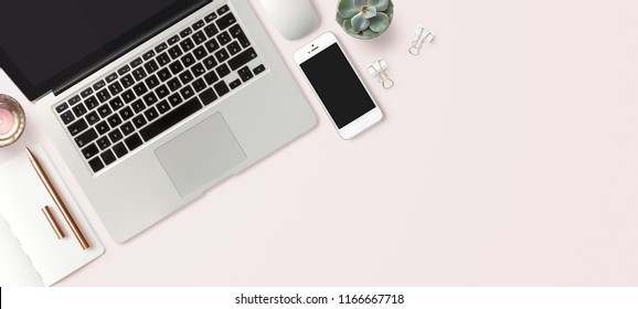 bright feminine banner / header with a stylish workspace with laptop computer, smartphone modern office accessories and a small succulent on a blush table, top view / flat lay