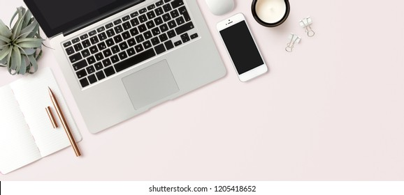 bright feminine banner / header with a stylish workspace with laptop computer, smartphone, modern office accessories and an air plant on a blush table, top view / flat lay