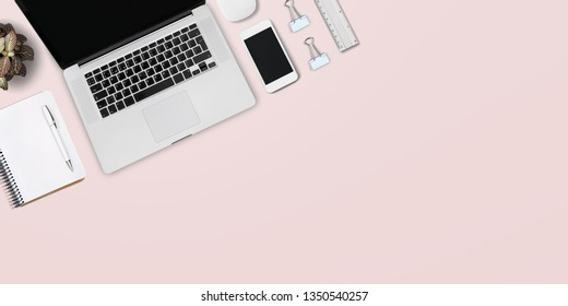 bright feminine banner / header with a stylish workspace with laptop computer, smartphone, modern office accessories and a small succulent on a blush table, top view / flat lay          - Image
