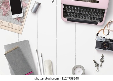 bright feminine desktop / workspace background with pink typewriter, notebooks, smartphone, camera and other accessories, top view