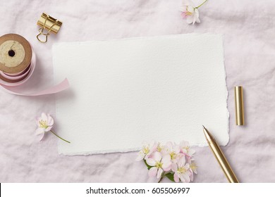 bright feminine spring stationery mockup scene with a handmade paper greeting card, golden accessories and cherry flowers on a soft pink fabric background