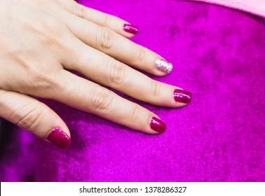 Bright festive drak pink manicure on female hands on magenta pillow. Nails design