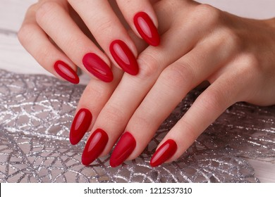 Bright festive red manicure on female hands. Nails design.