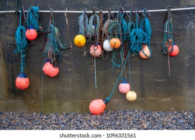 Bright Fishing Buoys and Line Hanging from a Harbour Wall