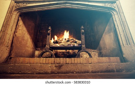Bright flame of fire burns in an old fireplace of a castle in England