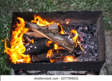 Bright flame of wood burning in brazier during the preparation for cooking on barbecue.