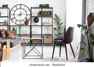 Bright flat interior in industrial style with big clock, potted plants, leather chair and decorations