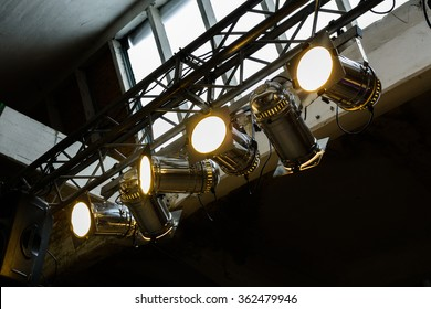 Bright floodlights attached to a steel frame. Horizontal view of yellow floodlights attached to a frame, used inside a hall.