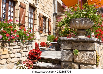Bright flower pots on an ancient stone house porch in Southern France