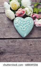 Bright flowers and  decorative heart  on vintage  wooden background. Selective focus. Place for text. Toned image.