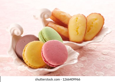 Bright food photography of macroons and madeleine on pink background