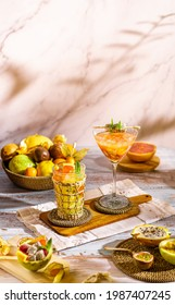 Bright food photography of tropical cocktails with natural juice. Backdrop with a basket with passion fruit, maracuya, physalis, orange, dragon fruit and lemon.