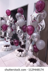A bright fountain of helium balloons of gray, burgundy, white, as well as mirrored silvery stars. To create a festive mood for the newlyweds. Happy wedding!