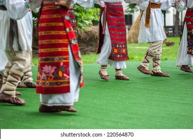 Bright fragment of fast Romanian folk dance with red girls skirts and traditional sandals