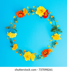 Bright frame made of yellow, orange flowers and petals on blue background. Flat lay, top view. Floral background.