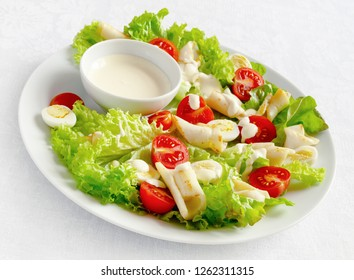 bright fresh salad with fried calamari, lettuce, tomatoes, and quile eggs dressed with mayo based sauce