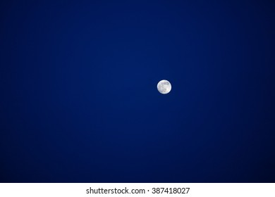 Bright full moon in the deep blue sky.