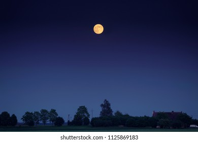 Bright full moon over scenic countryside with farm buildings at summer evening