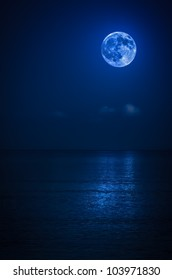 Bright full moon with reflections on a calm ocean at midnight