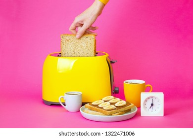 bright, fun breakfast. girl preparing toasts. yellow toaster and a cup of coffee on a pink background