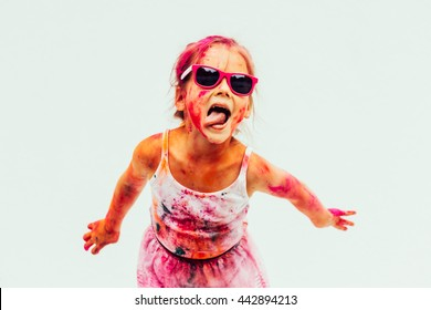 Bright and funny little girl playing with colors of Holi