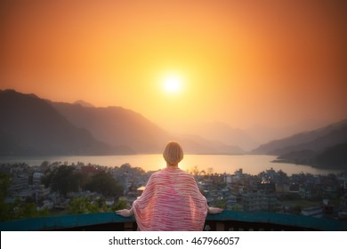 Bright future. Mature woman is standing on the terrace looking at the beautiful sunset over the lake and mountains.