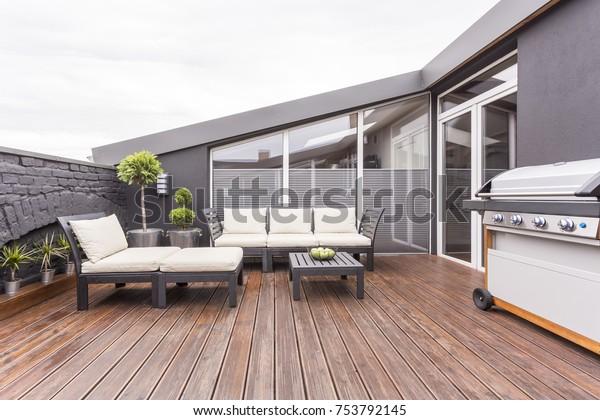Яркая садовая мебель, гриль и растения на уютной террасе с деревянным полом и кирпичной стеной