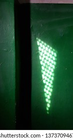 Bright geometric shadows on green painted wall near corner. Triangle light spot from window with dotted lattice. Blurred circles of lights inside triangle shadow background. Light and shadow concept