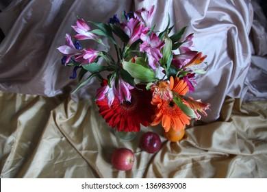 Bright gerberas, alsrtoemerias, irises, apple, orange on tender drape