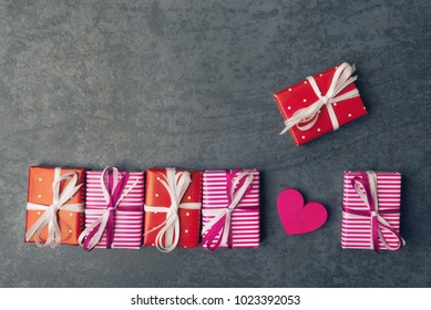 Bright gift boxes and Valentines heart on dark stone background.