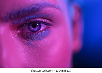 Bright girl model with blue eyes. Stylish makeup on the face blue background. Close Up Shoot.