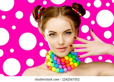 Bright girl model holding hands with manicure on her face. Beautiful, stylish, young woman in a candy doll style with massive beads around her neck