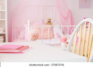 Bright girl room with desk, chair and pink canopy bed